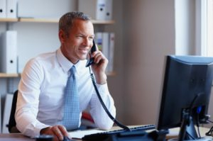 Happy mature business man using computer while talking on phone in the office